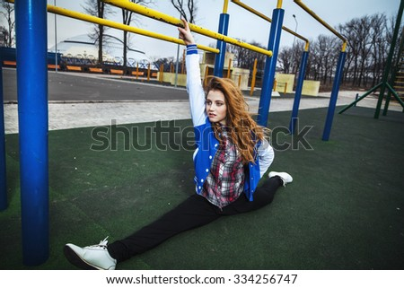 pretty girl doing splits exercise in a deserted town sports - stock photo