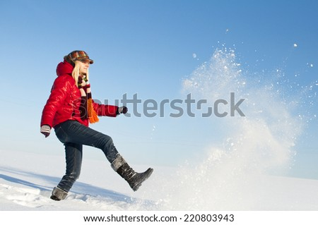 Pretty girl enjoys winter. Young girl throws snow footed in sunny winter day. - stock photo