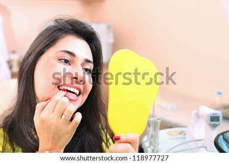 Pretty girl examines her teeth in the mirror - stock photo