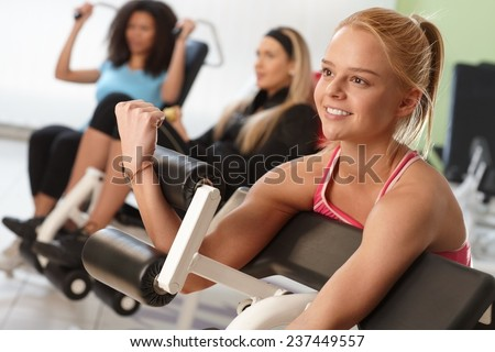 Pretty girl exercising on weight machine at the gym. - stock photo