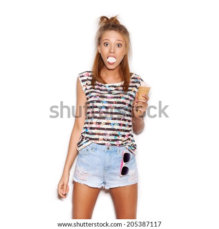 Pretty girl having fun and eating ice cream. Closed eyes, smiling. Indoors, not isolated - stock photo