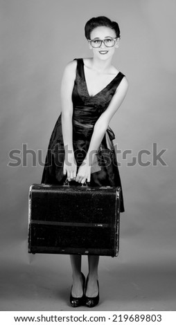 Pretty girl holding an old suitcase while wearing big red glasses in front of a grey background in black and white - stock photo