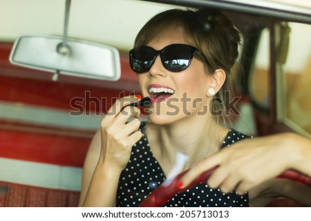 Pretty girl in a car. Cute blond woman applying lipstick in a car - stock photo