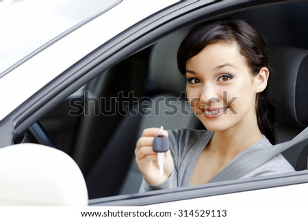 Pretty girl in a car showing the key - stock photo