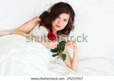 pretty girl in bed with red rose - stock photo