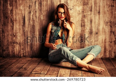Pretty girl in casual jeans clothes sitting on a wooden floor by the grunge wall. Fashion. - stock photo