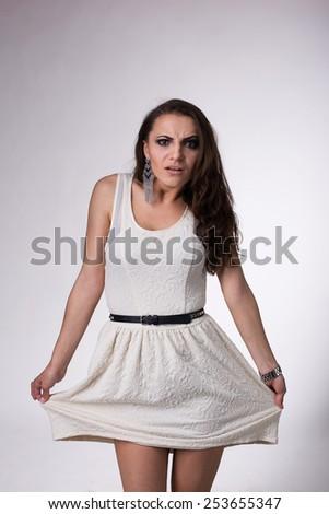 Pretty girl in dress making faces  in studio  - stock photo