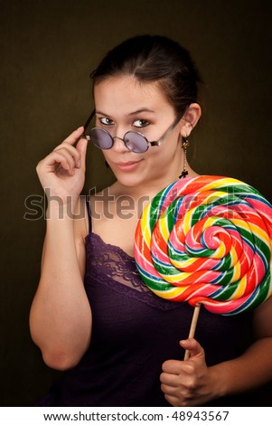 Pretty girl in funky purple outfit on green background with big lollipop - stock photo