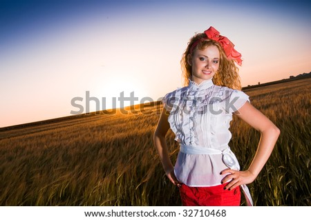 Pretty girl in golden wheat field - stock photo
