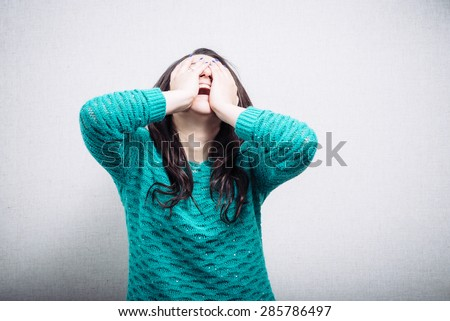 Pretty girl in hysterics covers her face - stock photo