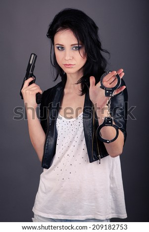 pretty girl in leather jacket with gun and handcuffs in hand on gray background - stock photo