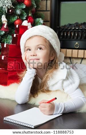 Pretty girl in Santa hat writes letter to Santa near christmas tree - stock photo