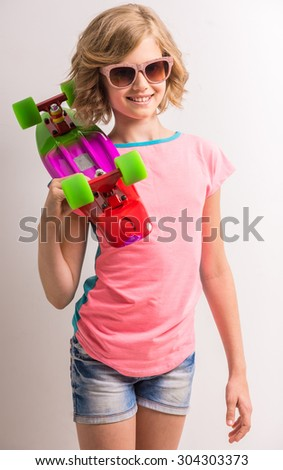 Pretty girl in sunglasses standing with skateboard on her shoulder in studio against white background. - stock photo