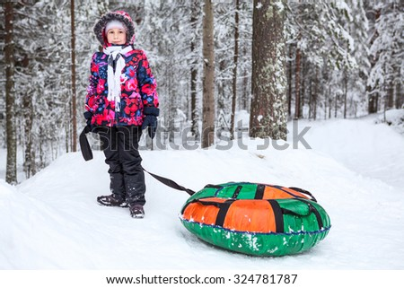 Pretty girl in warm clothes standing with tube for winter slope riding. Snowy forest - stock photo