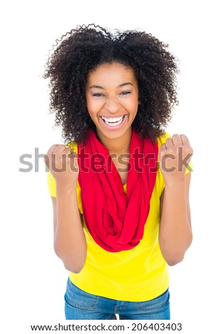 Pretty girl in yellow tshirt and denim hot pants cheering at camera on white background - stock photo