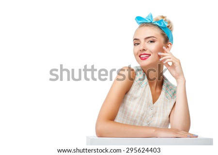 Pretty girl is sitting at small table. She is touching her face and smiling. Isolated on background and copy space in left side - stock photo