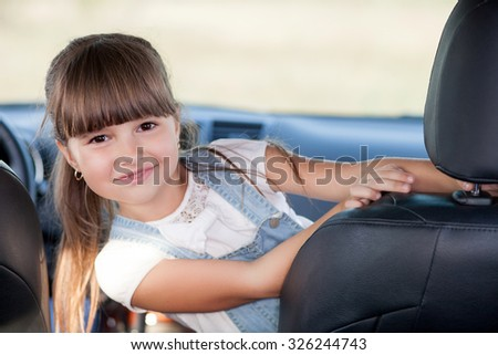 Pretty girl is sitting in car and posing. She is looking forward playfully and smiling - stock photo