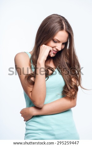 Pretty girl is smiling with shyness. She is looking down playfully. She is raising her hand to her cheek. Isolated on background - stock photo