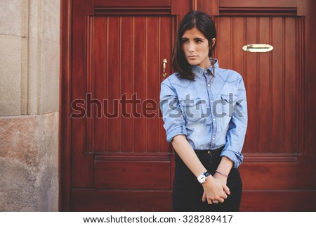 Pretty girl is standing in front of wooden door, gorgeous lady posing to a photographer. Fashionable street-style photo session. Trendy look of amazing female model on the background of ancient door  - stock photo