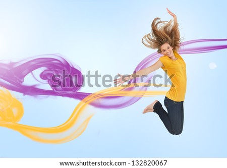 Pretty girl jumping for joy with purple and yellow smoke trails on blue background - stock photo
