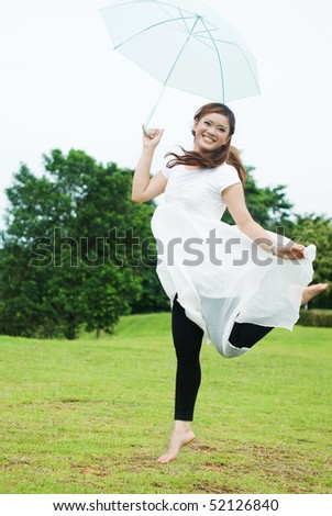 pretty girl jumping with umbrella - stock photo
