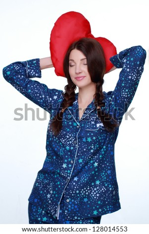 Pretty girl keeps a red pillow in blue pajamas in the form of heart on Holiday theme - stock photo