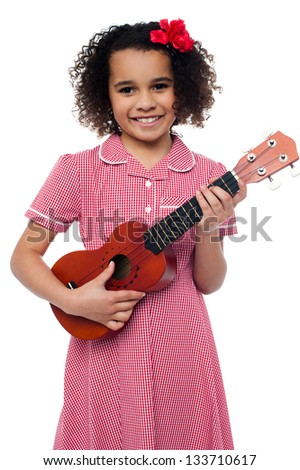 Pretty girl kid loves music. Holding toy guitar in hand. - stock photo