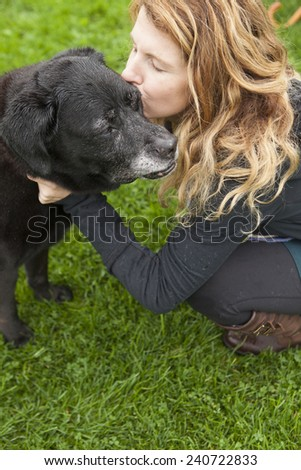 Pretty girl kissing her aging and  senior dog  - stock photo