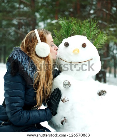 Pretty girl kissing snowman in pinewood on a winter day - stock photo
