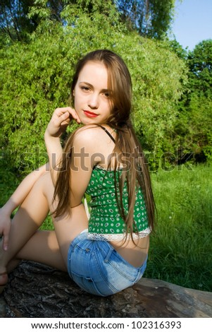 Pretty girl leaning against a tree in denim shorts and a t-shirt looks into the distance - stock photo