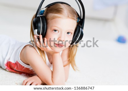 Pretty girl listening to music with headphones lying on the floor in the living room - stock photo