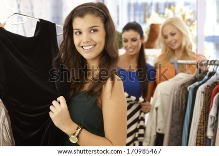 Pretty girl looking at black dress at clothes store smiling happy. - stock photo