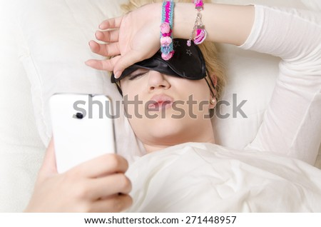 Pretty girl lying in bed pulling up sleeping mask to see what time is it/ wake up, or cant sleep concept - stock photo