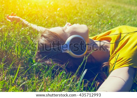 pretty girl lying in summer grass with headphones listening to music and relaxing - stock photo