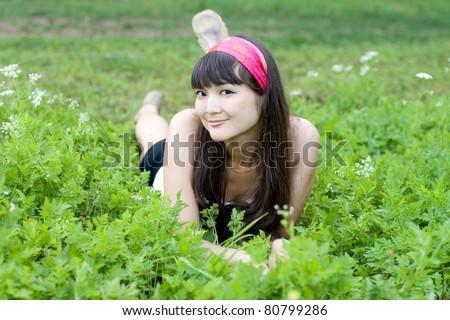 Pretty girl lying on grass - stock photo