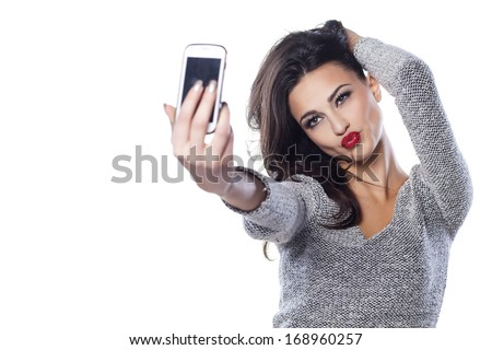 pretty girl make a duck face, and take a self portrait with her smart phone - stock photo