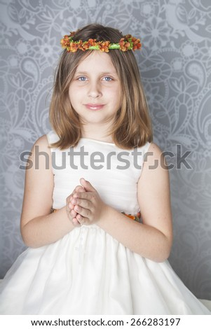 Pretty girl on the day of their communion in prayer with the rosary in his hands - stock photo