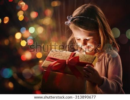Pretty girl opening magic giftbox on Christmas day - stock photo