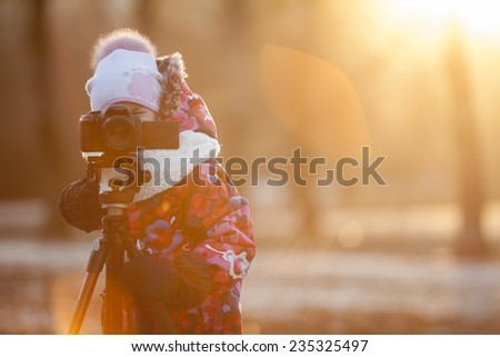 Pretty girl photographer taking pictures on camera using a tripod, sunset light, winter, copyspace - stock photo