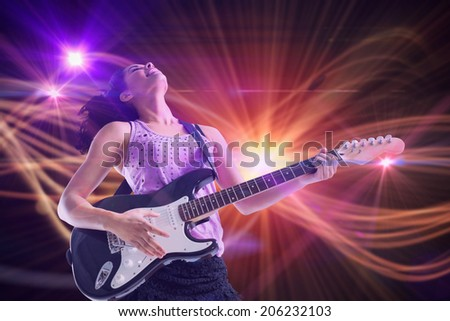 Pretty girl playing guitar against curved laser light design in orange - stock photo