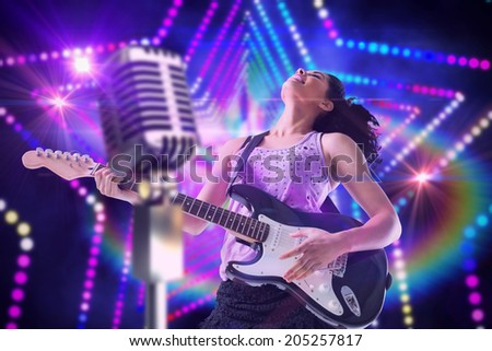 Pretty girl playing guitar against digitally generated star laser background - stock photo