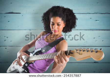 Pretty girl playing guitar against painted blue wooden planks - stock photo