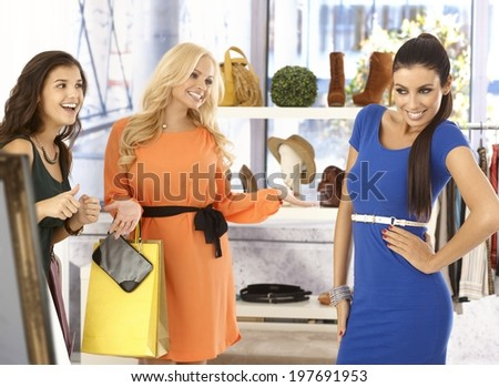 Pretty girl posing in new blue dress at clothes store, friends looking at her happy, all smiling. - stock photo