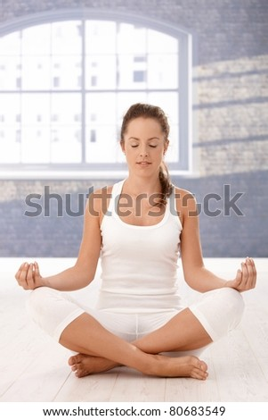 Pretty girl practicing yoga in studio, sitting on floor, meditating, eyes closed.? - stock photo