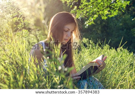 Pretty girl reading a book on a meadow - stock photo