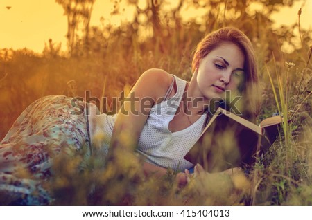 Pretty girl reading a book  on  a  meadow, russia - stock photo