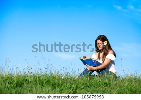 Pretty girl reading book and relaxing on grass with beautiful blue sky - stock photo