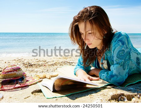 Pretty girl reading novel at beautiful beach - stock photo