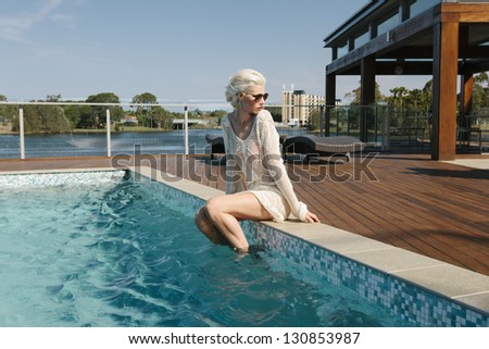 Pretty girl relaxing poolside - stock photo