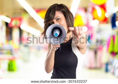 Pretty girl shouting with a megaphone on unfocused background - stock photo
